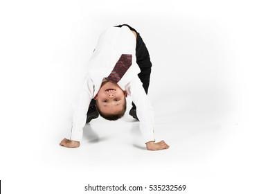 Little school kid doing fitness exercises. Studio portrait on white background
