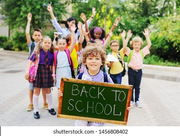 """little schoolboy with curly hair on the background of a group of children classmates holding a sign with the inscription """"back to school."""""""
