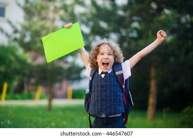 Little schoolboy rejoices. The boy raised up both hands. The student is smartly dressed. He looks at the camera with a smile. Behind the boy's backpack. Back to school.