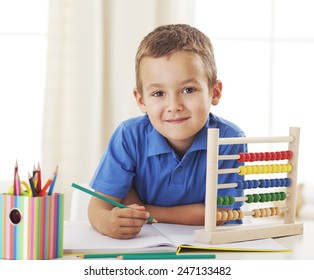 Little schoolboy sitting at a desk and studying