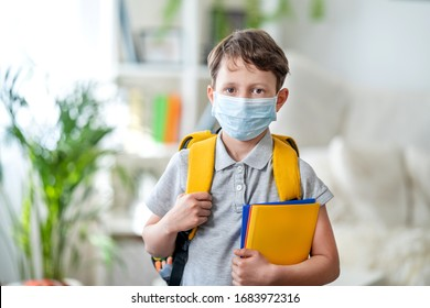 Little schoolboy wearing mask during corona virus and flu outbreak. llness protection for kids. Mask for coronavirus prevention. School kid coughing. Little boy breathes through mask, going to school.