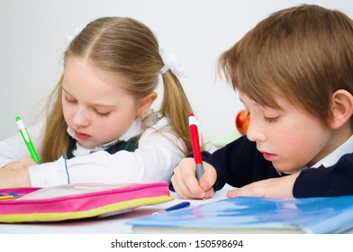 Little schoolchildren writing in workbook