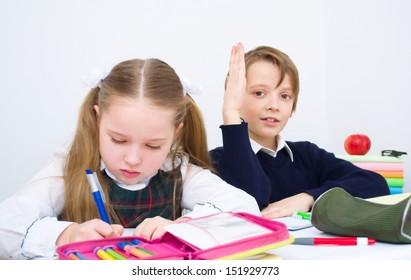 Little schoolchildren writing in workbook