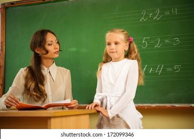 Little schoolgirl answering near blackboard in school