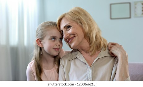 Little schoolgirl hugging grandmother and smiling, love and care in family