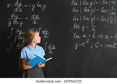 Little schoolgirl near blackboard in classroom