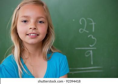 Little schoolgirl posing in front of a chalkboard