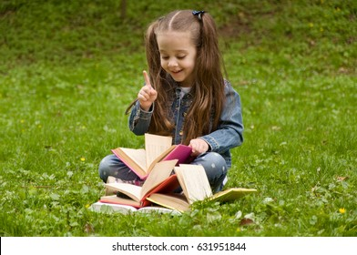 Little schoolgirl is reading book. Girl gives thumps up. Know how.