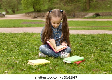 Little schoolgirl is reading a book in nature. Smart little pupil. Early development of children. Training and rest