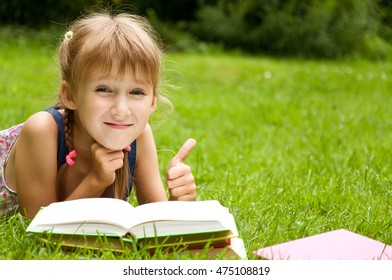 Little schoolgirl is reading a book. smart little pupil