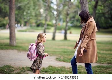 little schoolgirl runnig to her mother after first day of school