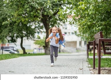 The little schoolgirl is running with a backpack and laughing. The concept of school, study, education, friendship, childhood.