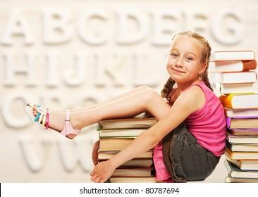 Little schoolgirl sitting on books