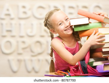 Little schoolgirl with stack of books