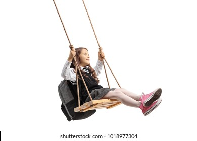 Little schoolgirl swinging on a wooden swing isolated on white background