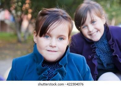 Little schoolgirl twins with pigtails outdoorsin the school park