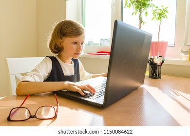 Little schoolgirl uses computer sitting at a desk at home. School, education, knowledge and children