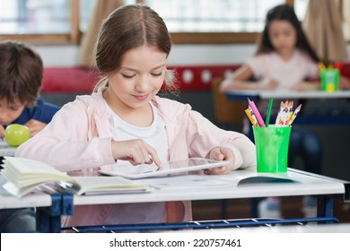 Little schoolgirl using digital tablet with classmates in background at classroom - Shutterstock ID 220757461