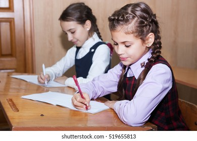 Little schoolgirl writing lesson in the classroom