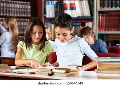 Little schoolgirls reading book together while sitting at table in library with classmates in background