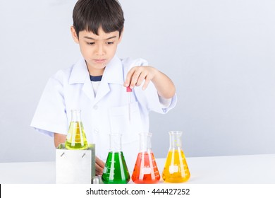 Little scientist boy with colorful flask on white table
