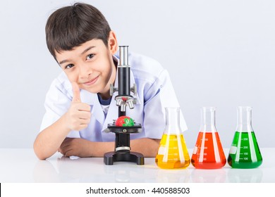 Little scientist boy with microscope and colorful flask on white table