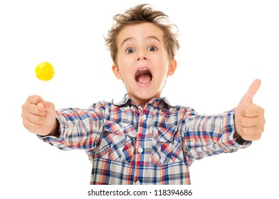 Little screaming excited boy shows thumb up with lollipop in hand  isolated on white