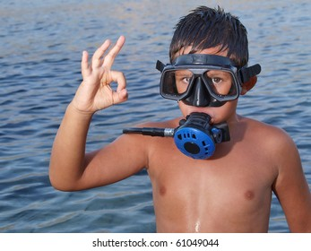 Little scuba diver giving an all ok sign before diving into beautiful blue adriatic sea