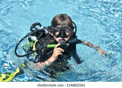 little scuba diver is looking into the camera while waiting for the adventure to start. diving lessons for beginners