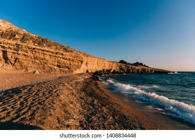 Little secret sea bay with rock in Greece with the summer sun. Blue water, clear blue sky and yellow sand. Summer vacation concept, recreation and travel, copy space.