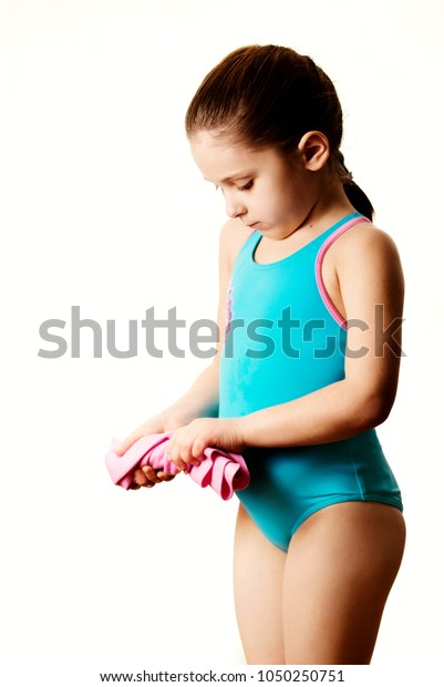 744b0e2cfda Little serious 7 years old cute caucasian girlie in cyan swimming costume  holding pink shammy,