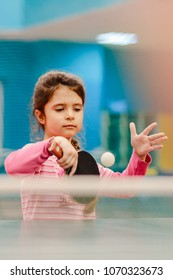 little serious girl playing table tennis in the tennis hall, tennis racket hitting the ball, the pitch of the ball