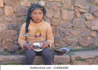Little serious native american girl holding plate with dinner outside.