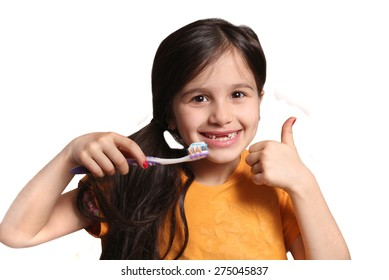 Little seven year old girl shows big smile showing missing top front teeth and holding a toothbrush with toothpaste and thumbs up on a white background