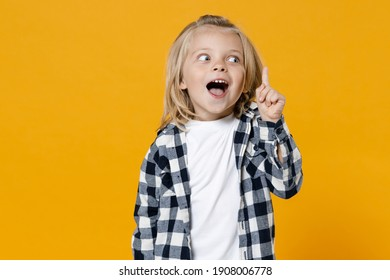Little shocked surprised wow fun happy blond long-haired kid boy 4-5 years old wearing casual clothes isolated on bright yellow wall color background children studio portrait. People childhood concept