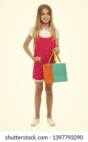 Little shopaholic. Girl smiling happy face carries shopping bag package, isolated white background. Kid girl long hair likes shopping. Shopping addicted concept. Child buy modern items in mall.