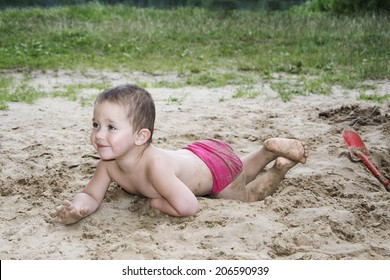 Little short-haired girl lying on the sand near the lake in summer and smiling.