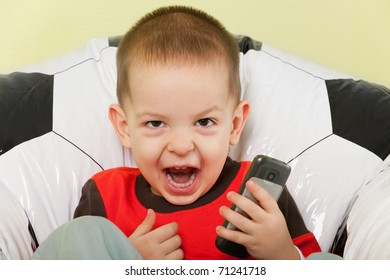 A little shouting boy is sitting on the football armchair