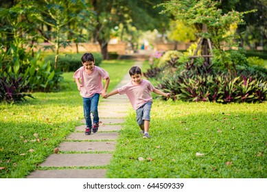 Little sibling asian boy running together in the park with happy together summer time