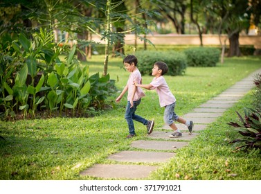 Little sibling boy playing together in the park