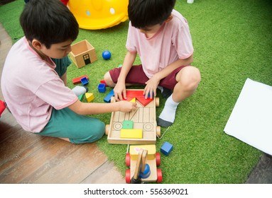 Little sibling boy playing toys in playroom class at school