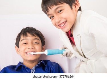 Little sibling boy pretend as a dentist Little sibling boy pretend as a dentist close up inside mouth check up