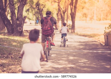 Little sibling boy riding bike together in the park
