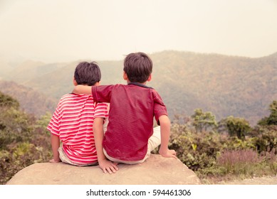 Little sibling boy sitting on the mountain