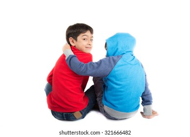 Little sibling boys sit together on white background