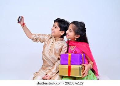 Little siblings in ethnic wear taking selfie on the occasion of Raksha bandhan festival celebrations - Shutterstock ID 2020376129
