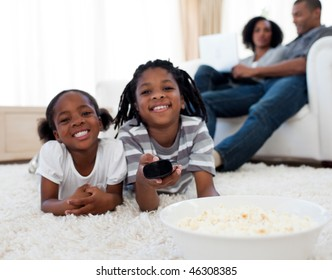Little siblings watching television and eating pop corn in the living room