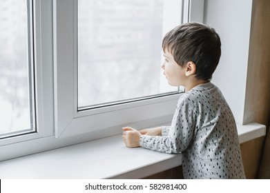 Little sick boy in gray pajamas looking through window