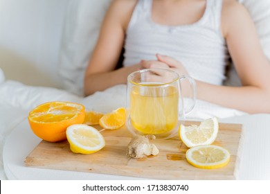 Little sick girl in bed with cup of antipyretic drugs for colds,flu.Tea with citrus vitamin C,ginger root,lemon,orange.Wooden tray. Home self-treatment.Medical quarantine covid-19 coronavirus therapy.
