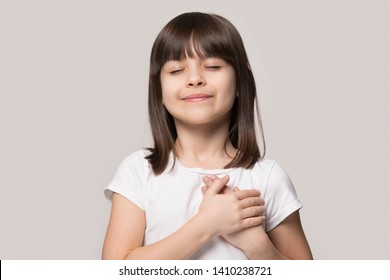 Little sincere adorable girl closed eyes holding hands on chest feeling gratitude pose isolated on sandy color beige background, arms on heart gesture of love appreciation gratitude, adoption concept